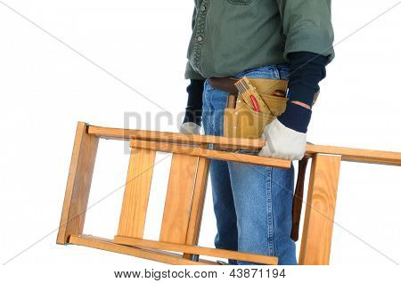 Closeup of a construction worker carrying a wooden ladder in his hand.  Horizontal format on a white background. Man is unrecognizable.