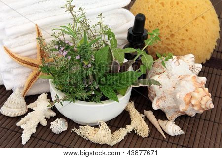 Aromatherapy and bathroom accessories with herb and flower leaf sprigs in a mortar with pestle,   over bamboo background.