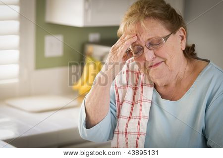Sad Crying Senior Adult Woman At Kitchen Sink in Home.