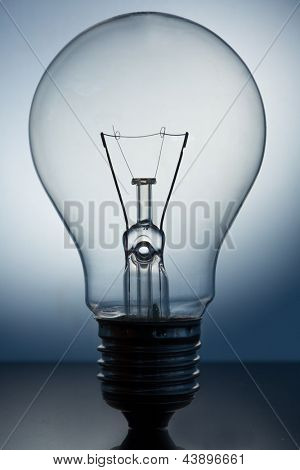 Close up of big light bulb standing on reflective surface