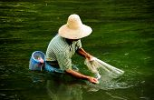 Chinese fisherman with hat and net in green water in China poster