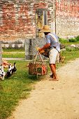 old chinese man with ducks and a cage at countryside in china poster