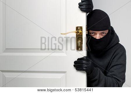 Home burglary concept with a burglar sneaking in a open house door