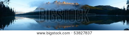 Panoramic Image Of Lucerne Peak Lit By The Rising Sun Reflected In Yellowhead Lake