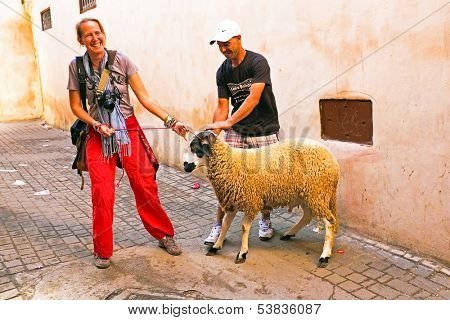FES, MAROCCO - October 15 2013 : Man and woman with their sheep on Eid al-Adha. The festival is celebrated by sacrificing a sheep and distributing the meat to relatives, friends, and the poor.
