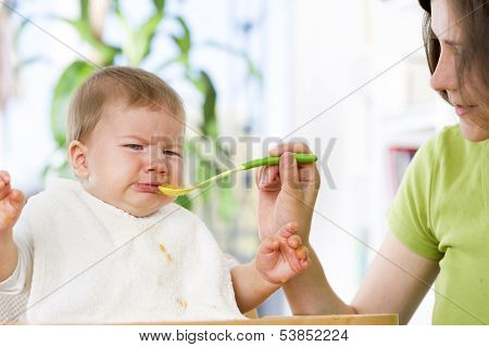 Crying baby boy refusing to eat food from spoon with hands dirty of vegetable puree.