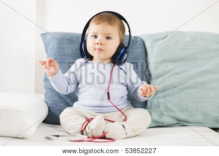 Adorable baby boy listening music at earphones while holding his hands in the air like a conductor.