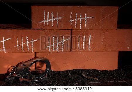 Counting days by drawing sticks on bricks on dark background