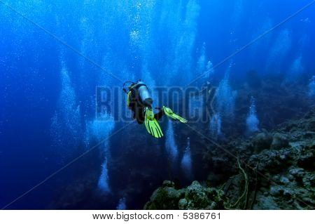 Diver Gliding Against Bubbles