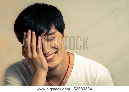 Young man covering his face and smiling