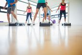 Low section of instructor with fitness class performing step aerobics exercise in gym poster