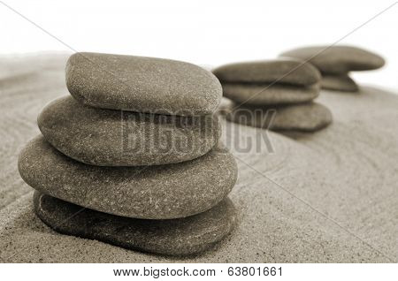 some piles of balanced stones in a zen garden