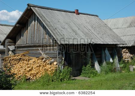 Old wooden shack with stack of firewood