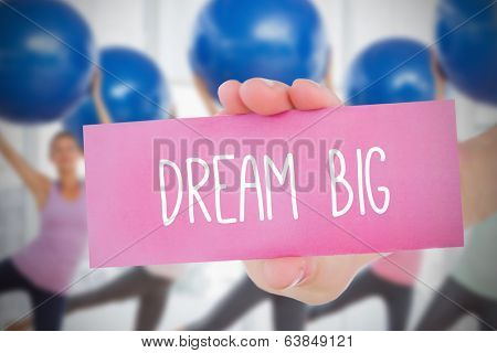 Woman holding card saying dream big against fitness class in gym poster