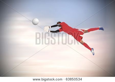 Goalkeeper in red making a save against beautiful blue cloudy sky poster