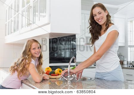 Young girl helping her mother to wash vegetables in the kitchen at home