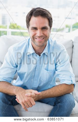 Happy handsome man sitting on the couch looking at camera at home in the living room