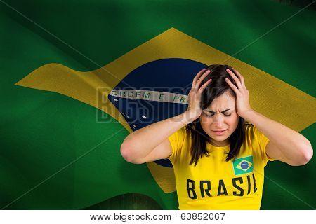 Upset football fan in brasil tshirt against digitally generated brazil national flag poster