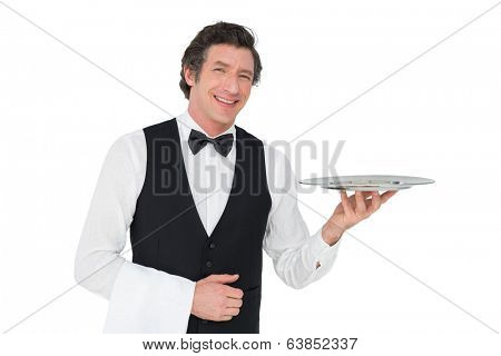 Portrait of happy waiter holding tray against white background