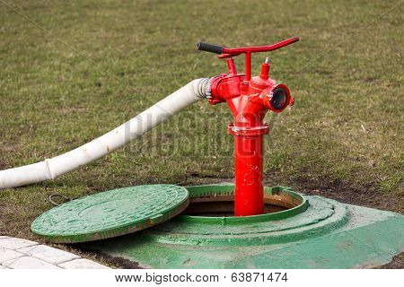 Red Fire Hydrant Stands In Manhole