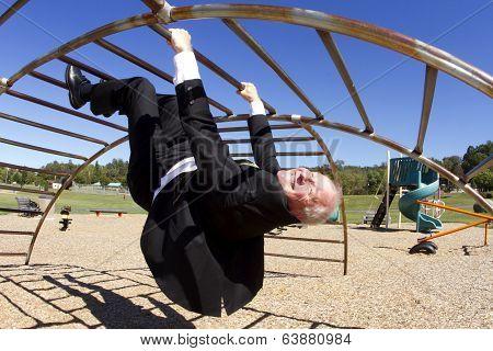 Businessman Upside Down in Playground