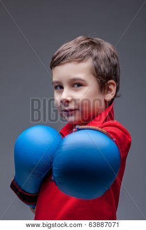 Slyly smiling young boxer posing looking at camera