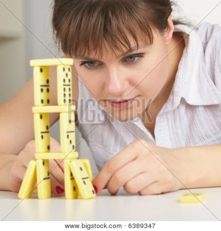 Young Woman Accurately Builds Tower Of Dominoes