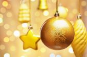 Golden Christmas Ornaments hanging with blur light on background poster