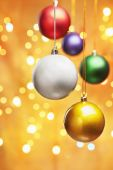 Colorful Christmas ornaments with golden background filled by blurred light poster
