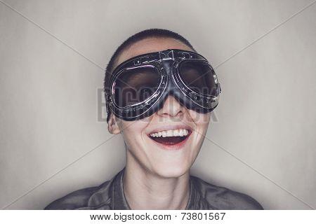 happy girl in retro pilot glasses over grey background