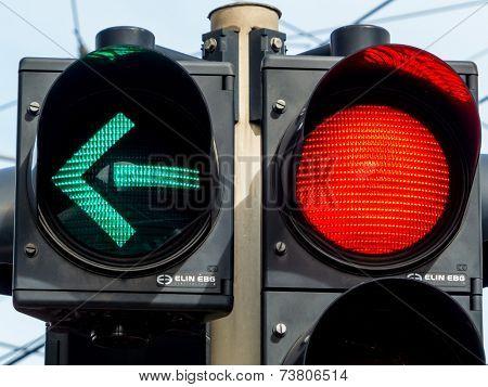 a traffic light with retoem light. green light for traffic turning left.