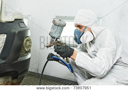 automobile repairman painter painting car body bumper in chamber poster