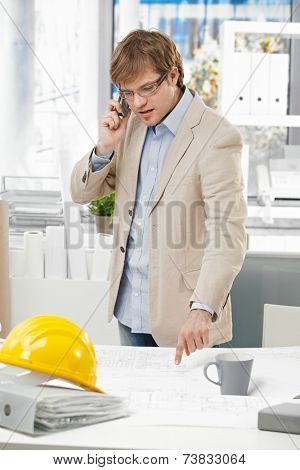 Young caucasian engineer talking on mobile phone and pointing at plan at office. Folder and hardhat on table.