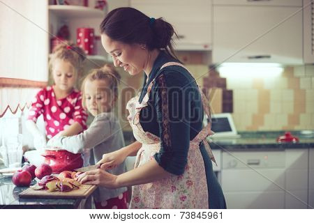Mother with her 5 years old kids cooking holiday pie in the kitchen to Mothers day, casual lifestyle photo series in real life interior