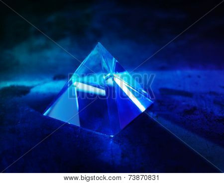 Glass prism with intensive light coming through. refractions of light in a glass prism. Focus is front edge.