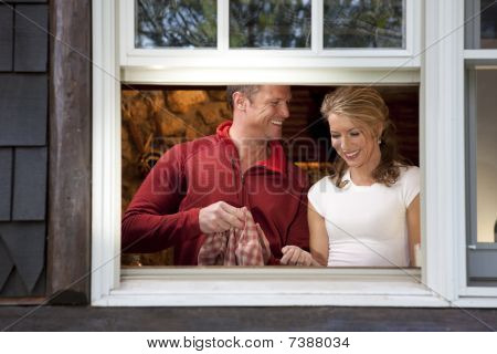 Smiling Couple Doing Dishes At Kitchen Window