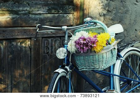 Old bicycle with flowers in metal basket on old brown door background