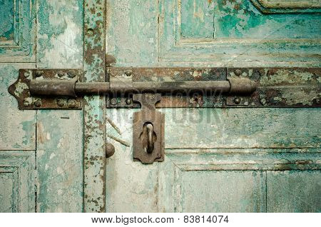 Rusted keyhole on green wooden door