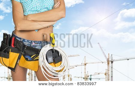 Woman in tool belt stands his arms crossed. Cropped image. Tower cranes as backdrop