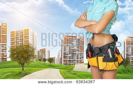 Woman in tool belt. Cropped image. Green hills with road and high-rise residential buildings as back