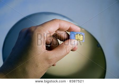 Hand Holding SIM Module Over Silicon Wafers