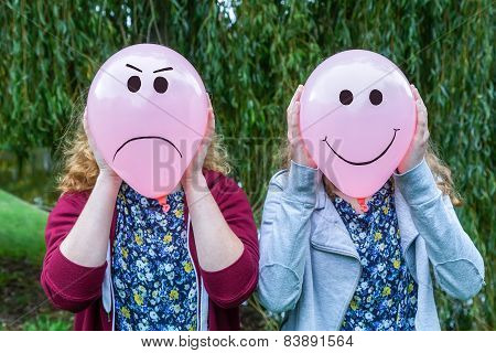 Two teenage girls holding balloons with facial expressions