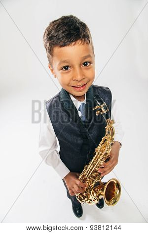 6 years old boy plays saxophone at studio top view looking at camers wide angle
