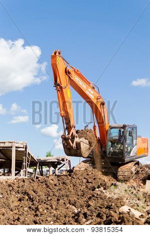 Orange Hitachi Digger Moving Soil