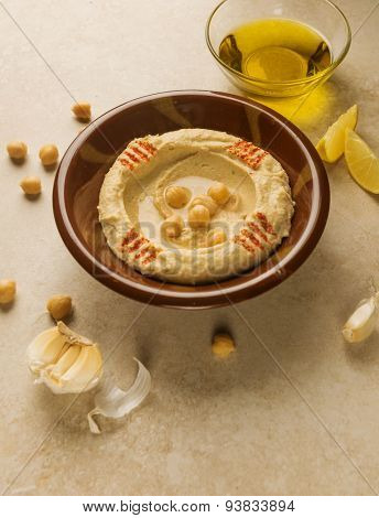 Hummus- Middle  eastern dip or spread made with chickpeas, garlic, lime, olive oil and tahina. Raw ingredients spread around the traditional hummous bowl.