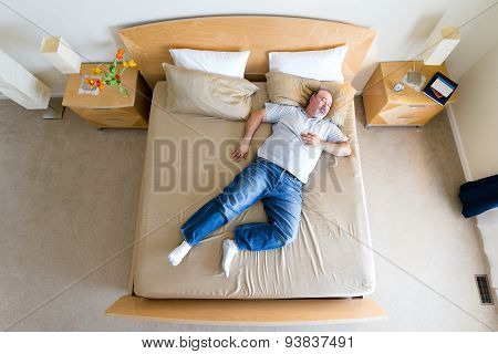 Overhead view of a big overweight middle-aged man with a goatee lying sprawled diagonally in his socks on a king size bed taking a midday nap over the weekend poster