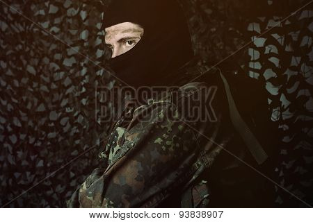 Camouflage Army Soldier With Dirty Face And Baclava Looking Sideways
