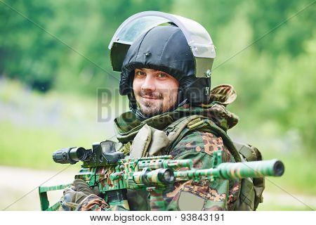 military. portrait of soldier in uniform with assault rifle outdoors