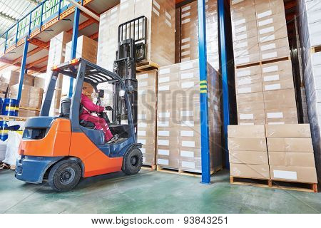 warehouse worker driver in uniform stacking cardboxes by forklift stacker loader poster