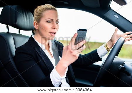 Woman texting while driving angrily her car, looking in rage on his phone instead of traffic